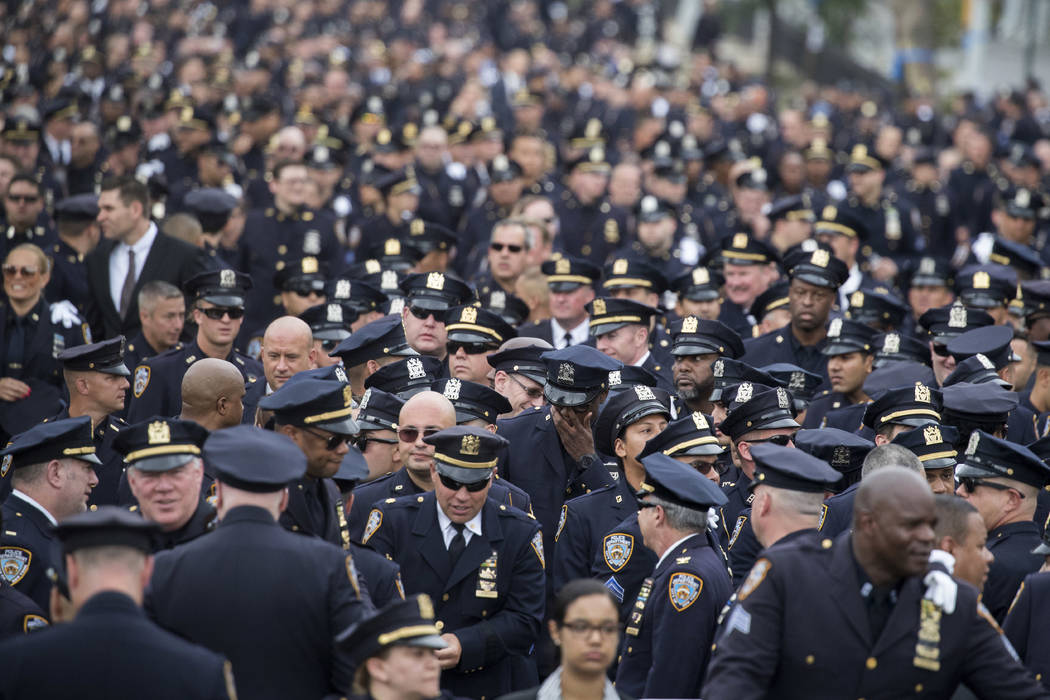 Police officers congregate for the funeral service for New York City slain police officer Miosotis Familia, Tuesday, July 11, 2017, at the World Changers Church in the Bronx borough of New York. F ...