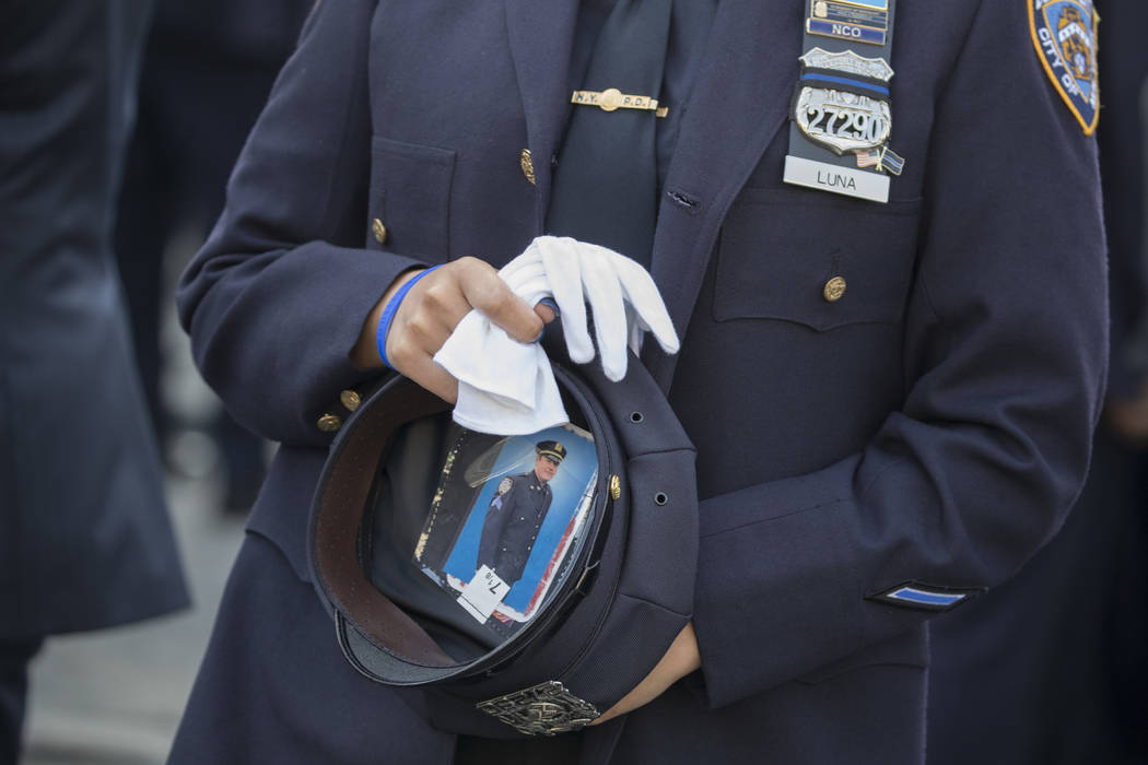 Police officer a Jennifer Luna carries a photo of slain Sgt. Paul Tuozzolo in her hat while paying her respects before the funeral service for slain police officer Miosotis Familia, Tuesday, July  ...