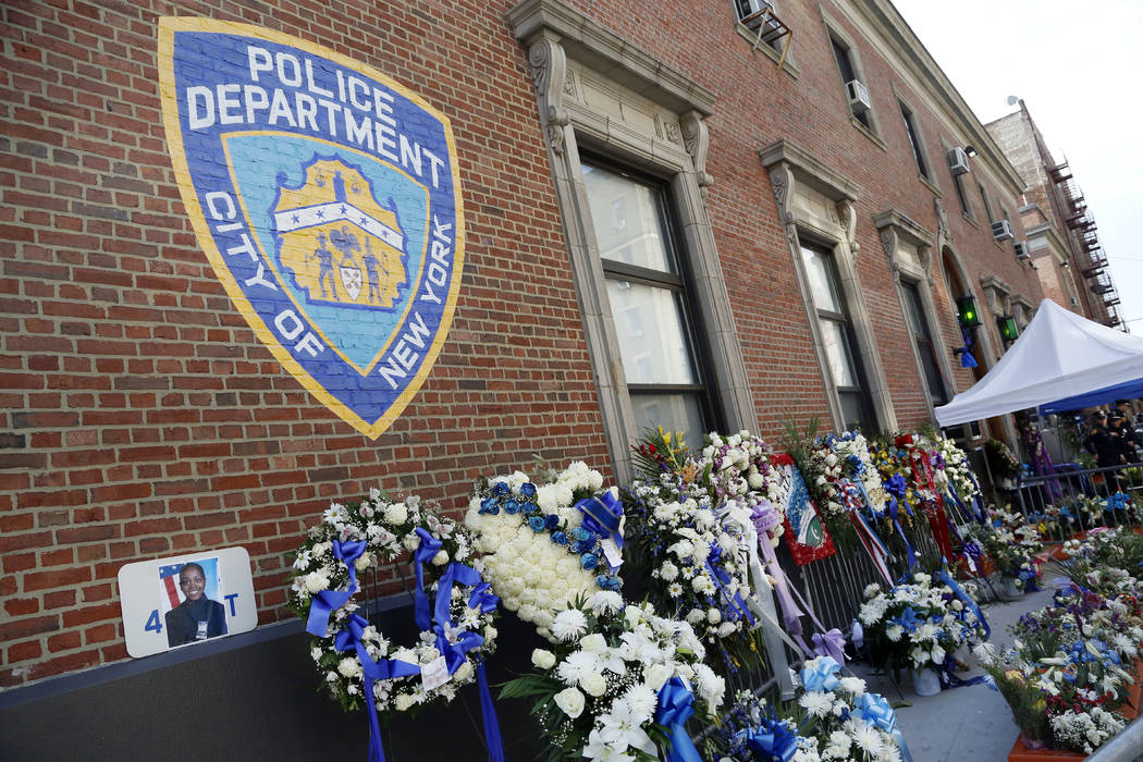 Memorial flowers are placed in honor of New York Police officer Miosotis Familia, Tuesday, July 11, 2017, outside the 46th Precinct in the Bronx borough of New York. Familia was on duty in the Bro ...