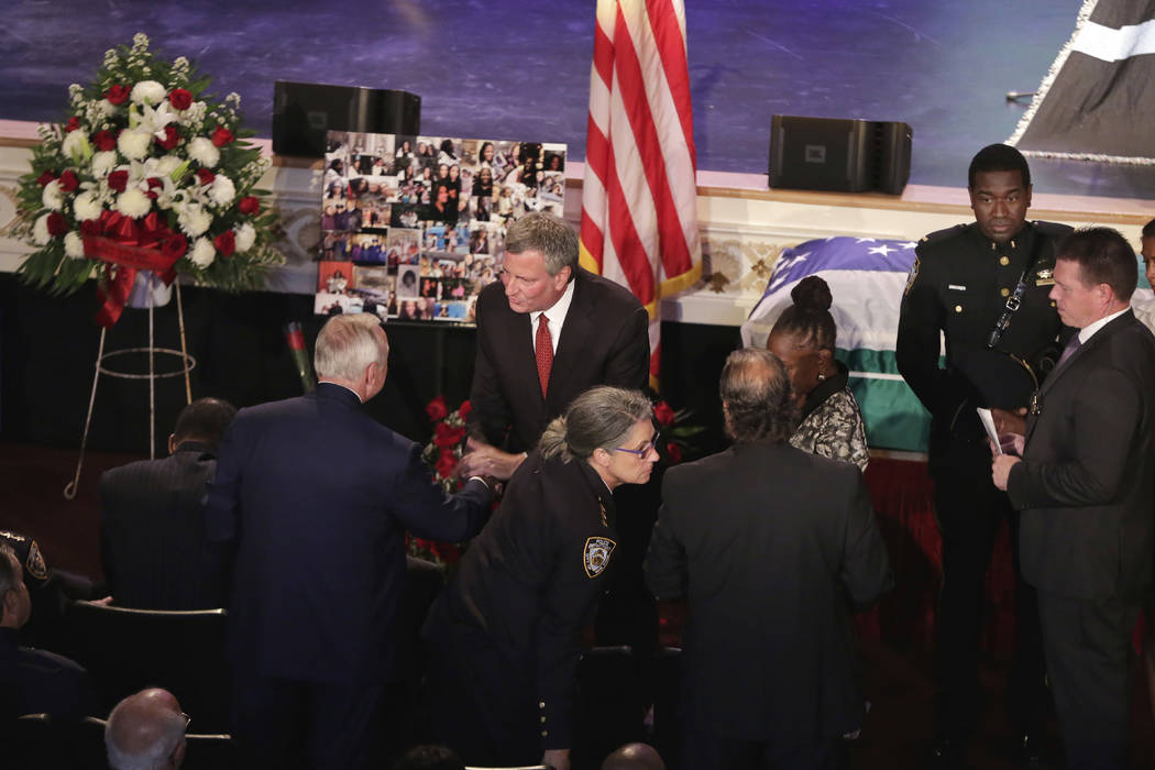 New York City Mayor Bill deBlasio, standing center, greets former New York City Police Commissioner William Bratton as he arrives for the funeral for New York City Police Officer Miosotis Familia, ...