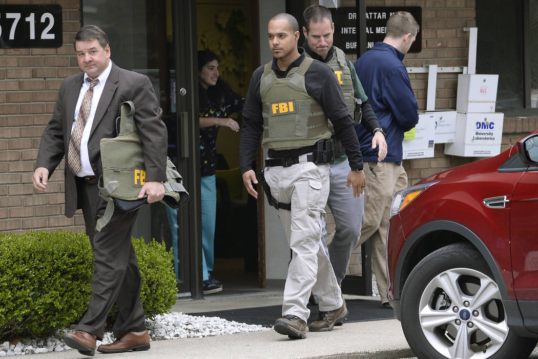 FBI agents leave the office of Dr. Fakhruddin Attar at the Burhani Clinic in Livonia, Mich. Friday, April 21, 2017, after completing a search for documents. The investigation is connected with the ...