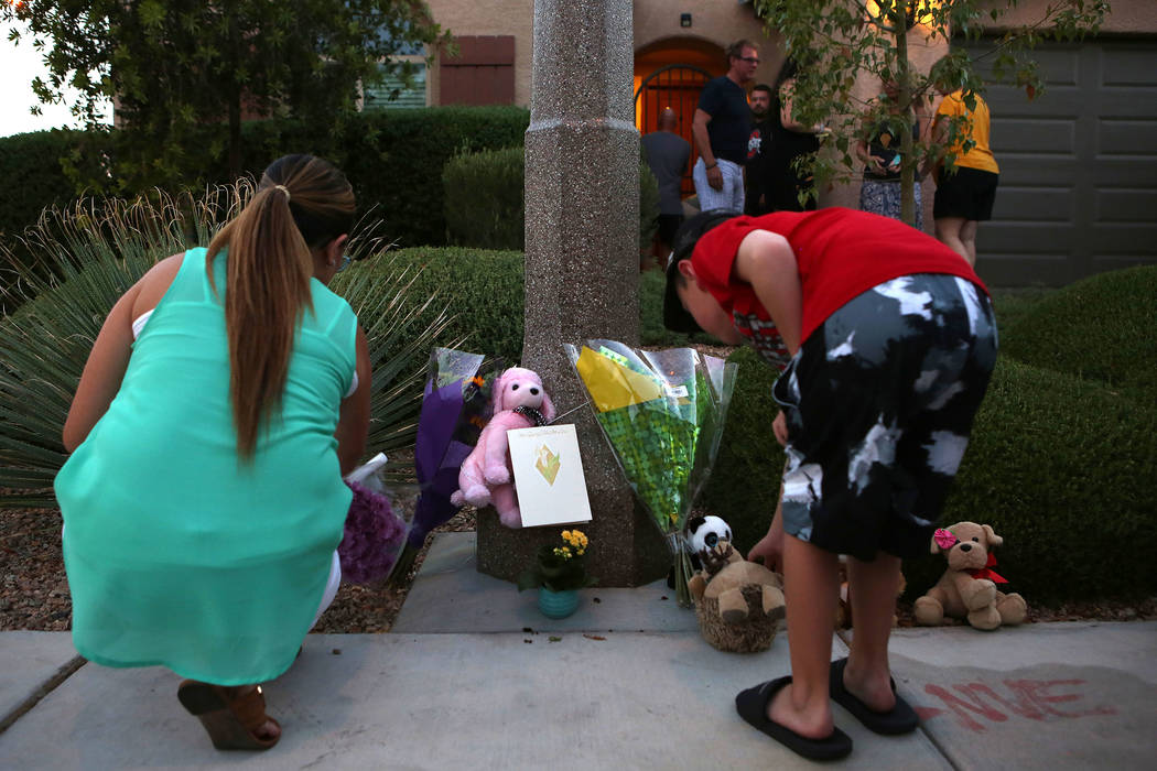 People stop by a makeshift memorial on the 10300 block of Numaga Road in Las Vegas, Tuesday, July 11, 2017, during a vigil for the family killed in Monday night's murder-suicide.  Bridget Bennett  ...