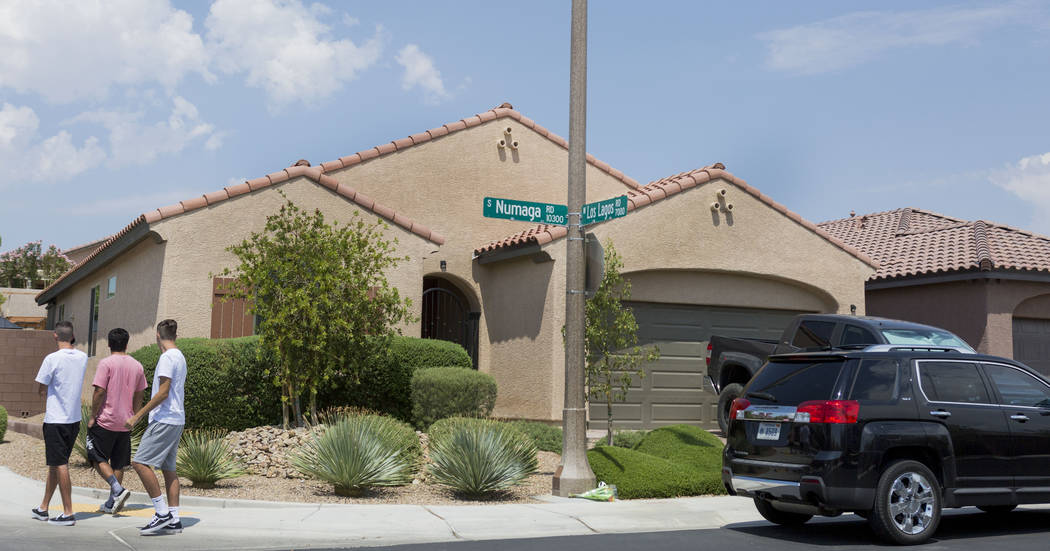 People walk passed the home of John Lunetta, 10337 S. Numaga Road, where the bodies were found Monday night  in Las Vegas, Tuesday, July 11, 2017. Las Vegas police said a man fatally shot his girl ...