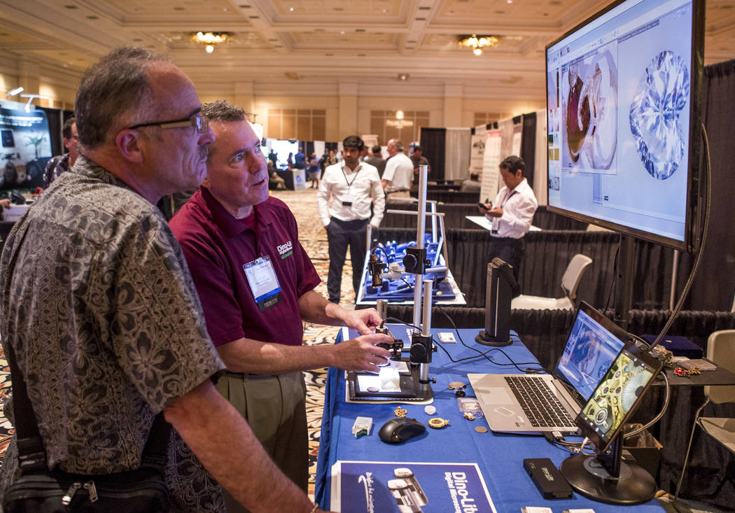 Joe Kane of Dino-Lite Scopes, center, shows a computer viewing system for jewelry and diamonds to Dave Newman at Pawn Expo at The Mirage on Wednesday, July 12, 2017.  Patrick Connolly Las Vegas Re ...