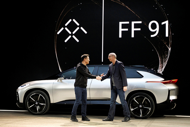 YT Jia (L), founder and CEO of LeEco, shakes hands with Nick Sampson, senior vice president of product R&D and engineering at Faraday Future, in front of a Faraday Future FF 91 electric car du ...
