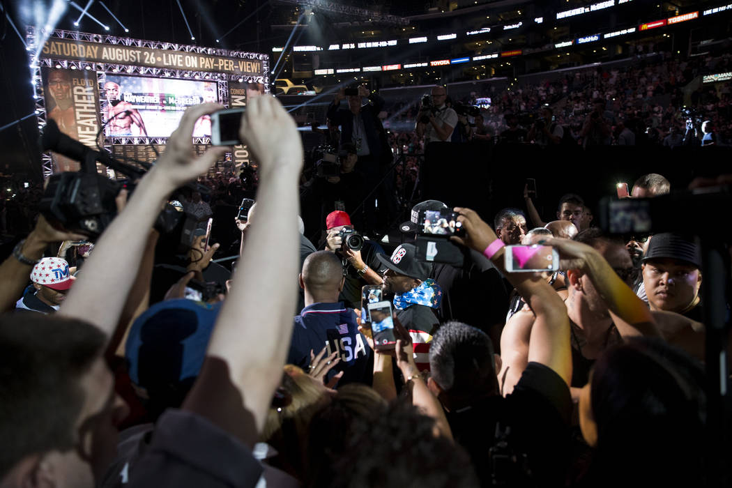 Boxer Floyd Mayweather Jr., center, was to the stage for a world tour event stop to promote his upcoming fight against UFC fighter Conor McGregor, at Staples Center in Los Angeles, Calif., on Tues ...
