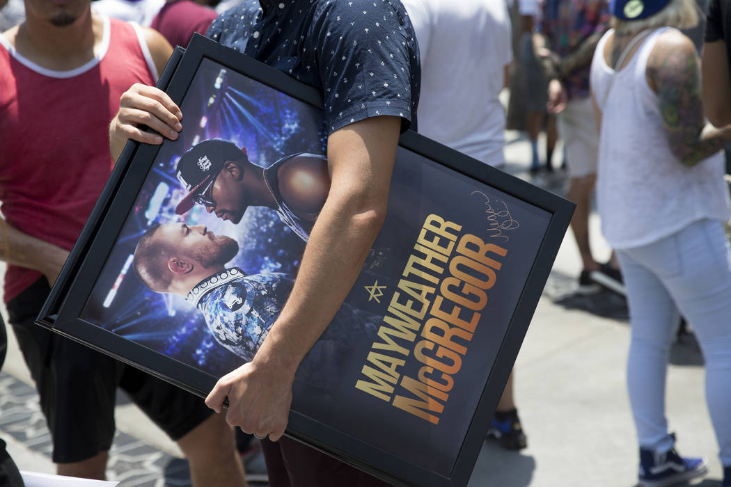 Fans in line to enter the Staples Center for the Floyd Mayweather Jr. and UFC fighter Conor McGregor world tour event to promote their upcoming fight, in Los Angeles, Calif., on Tuesday, July 11,  ...