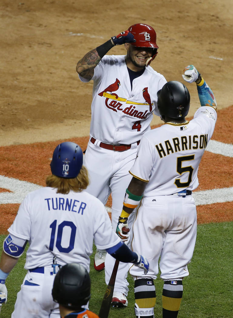 National League's St. Louis Cardinals catcher Yadier Molina (4), is congratulated by Pittsburgh Pirates Josh Harrison (5) and Los Angeles Dodgers Justin Turner (10), after hitting a home run in th ...