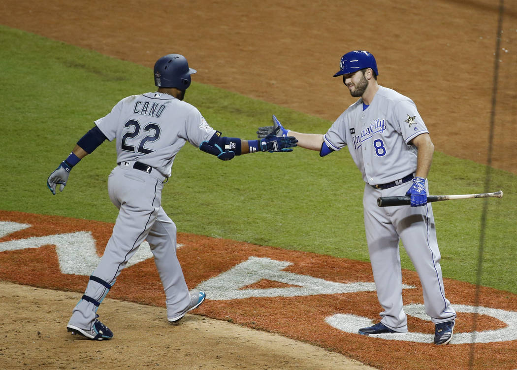 American League's Seattle Mariners Robinson Cano (22), is congratulated by Kansas City Mike Moustakas, after Cano hit a home run in the 10th inning, during the MLB baseball All-Star Game, Tuesday, ...