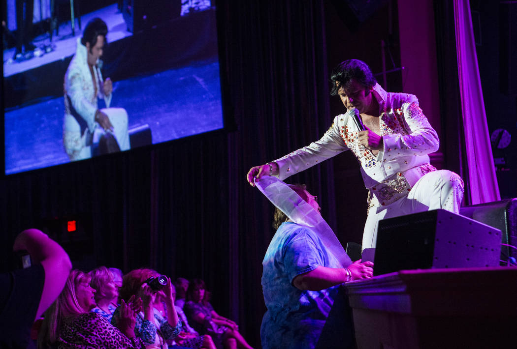 Elvis impersonator James King hands a scarf to an audience member while performing during the tribute artist contest at the Images of the King festival at Sam's Town in Las Vegas on Saturday, July ...