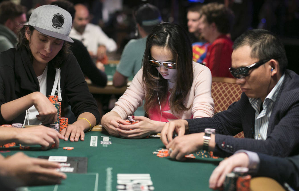 Jessica Ngu (center) from Singapore, Australia checks her cards during day five of the World Series of Poker at The Rio All-Suite Hotel and Casino in Las Vegas, Saturday, July 15, 2017. Gabriella  ...