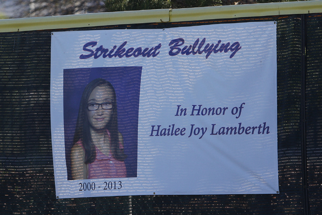 A sign on the outfield wall honors the memory of Hailee Joy Lamberth, the little girl who committed suicide as a result of being bullied, during a baseball game at the Arroyo Grande Sports Complex ...