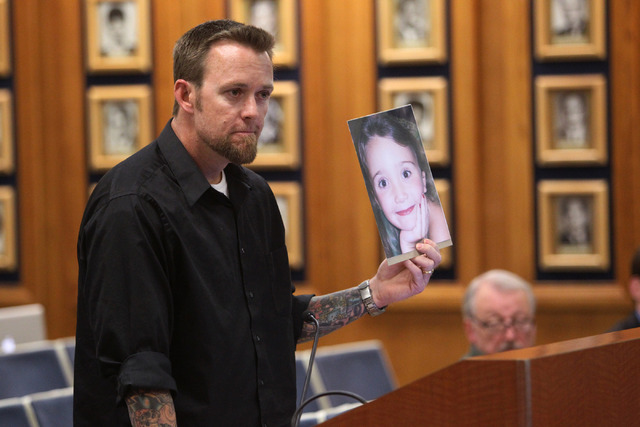 Jason Lamberth speaks to the Clark County School Board Thursday, while holding a photograph of his 13-year-old daughter, Hailee Lamberth, who killed herself Dec. 12. Lamberth said that he hadn't ...