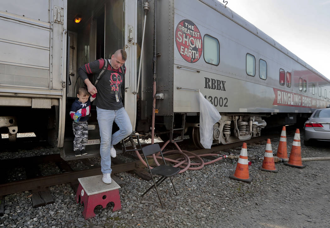 Boss clown Sandor Eke helps his 2-year-old son. Michael Eke step off the Ringling Bros. circus red unit's traveling train parked in a rail yard as they head to the arena for a show, Thursday, May  ...