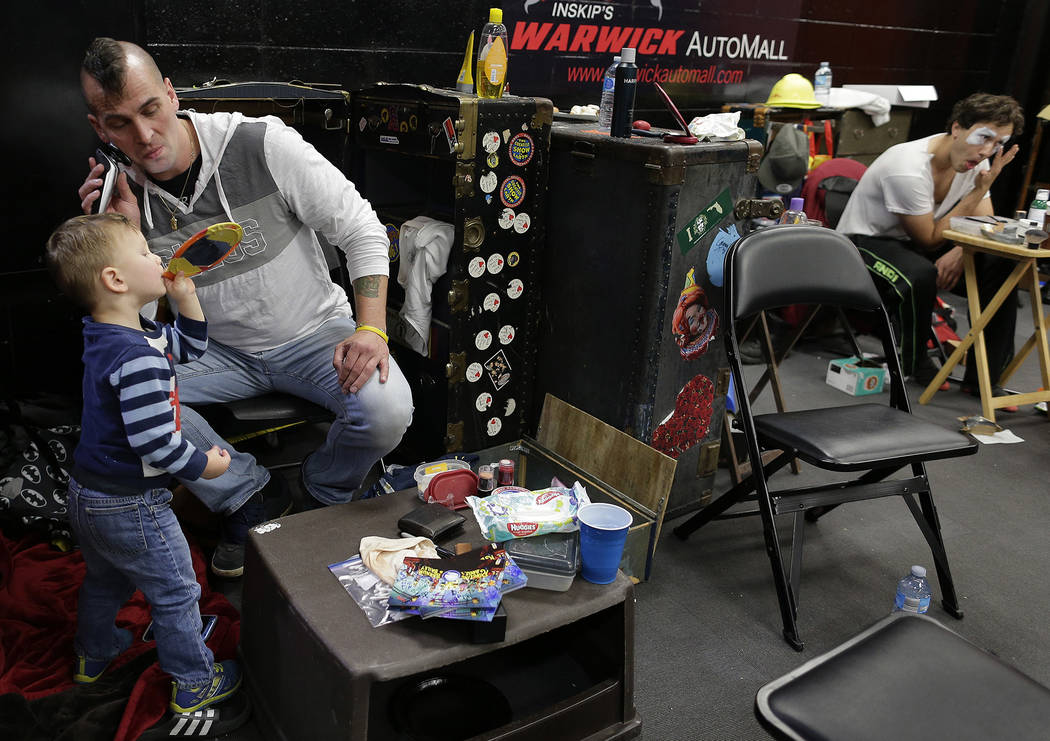 Boss clown Sandor Eke, left, shaves with help from his 2-year-old son, Michael, before putting on his makeup before the opening performance, Friday, May 5, 2017, in Providence, R.I. Eke performed  ...