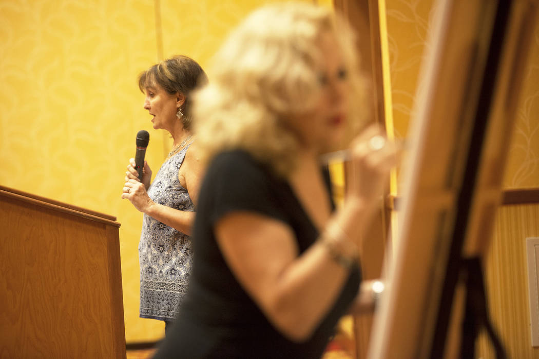"""Artist Meegan Boiros paints according to the passage that author Linda Lou reads during an event, Painted Stories ҅ndless Summer,"""" on Sunday, July 16, 2017, at the South Point.  Rac ..."""