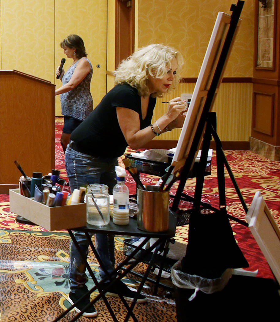 "Author Linda Lou speaks while artist Meegan Boiros paints during an event, Painted Stories ""Endless Summer,"" on Sunday, July 16, 2017, at the South Point.  Rachel Aston Las Vegas R ..."