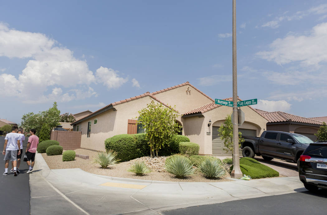 People walk passed the home of John Lunetta, 10337 S. Numaga Road, where the bodies were found Monday night  in Las Vegas, Tuesday, July 11, 2017. Elizabeth Brumley Las Vegas Review-Journal