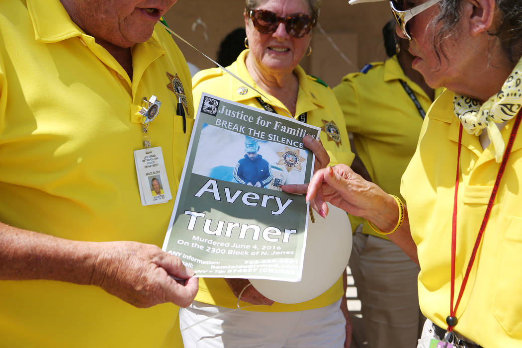 Police volunteers read a poster of an event in remembrance of Avery Turner on Thursday, July 13, 2017, in Las Vegas. Turner was found fatally shot on a median at Jones Blvd near Lake Mead Blvd las ...