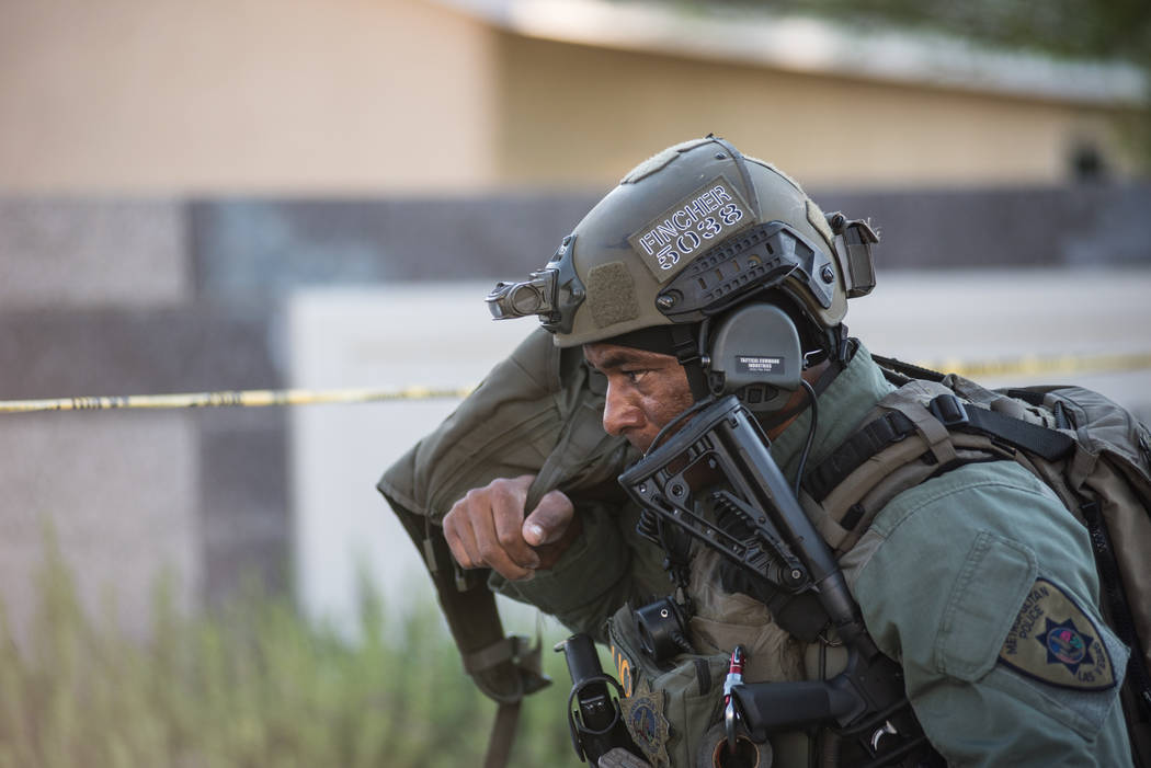 A Las Vegas police officer works to apprehend a person who fired shots at officers in a residential area near Clark County Wetlands Park, Wednesday, July 12, 2017. (Morgan Lieberman Las Vegas Revi ...