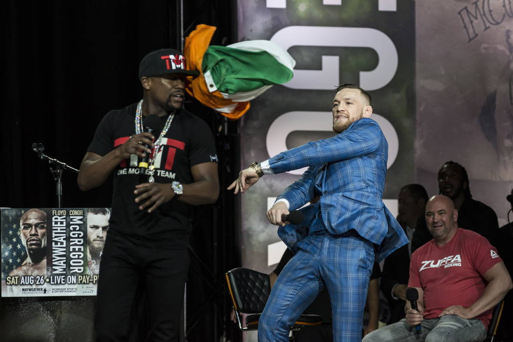 Conor McGregor, right, throws an Irish flag at Floyd Mayweather during a promotional stop in Toronto on Wednesday, July 12, 2017, for their upcoming boxing match in Las Vegas. (Christopher Katsaro ...
