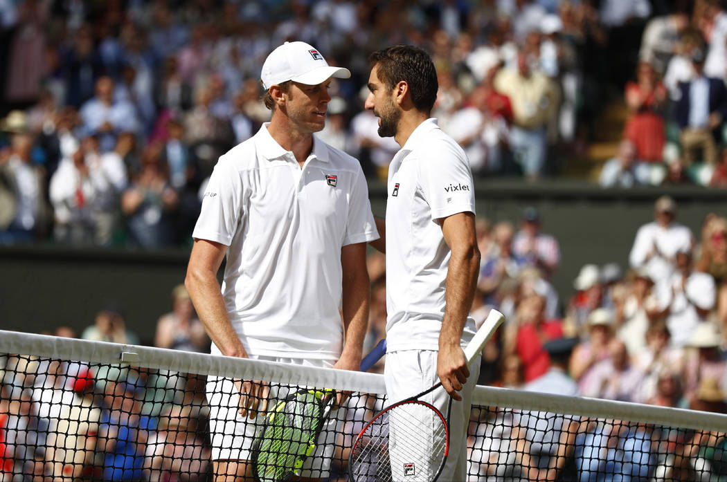 Croatia's Marin Cilic, right, greets Sam Querrey of the United States at the net after winning their Men's Singles semifinal match on day eleven at the Wimbledon Tennis Championships in London, Fr ...