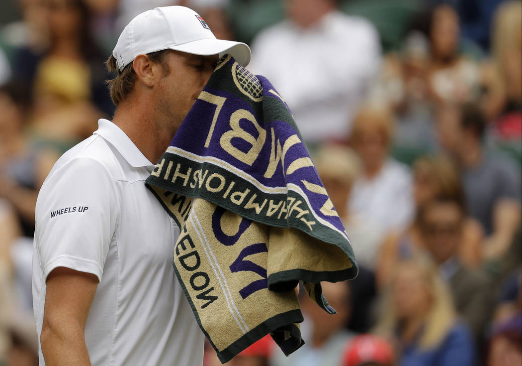Sam Querrey of the United States wipes his face as he plays his Men's Singles semifinal match against Croatia's Marin Cilic on day eleven at the Wimbledon Tennis Championships in London Friday, Ju ...