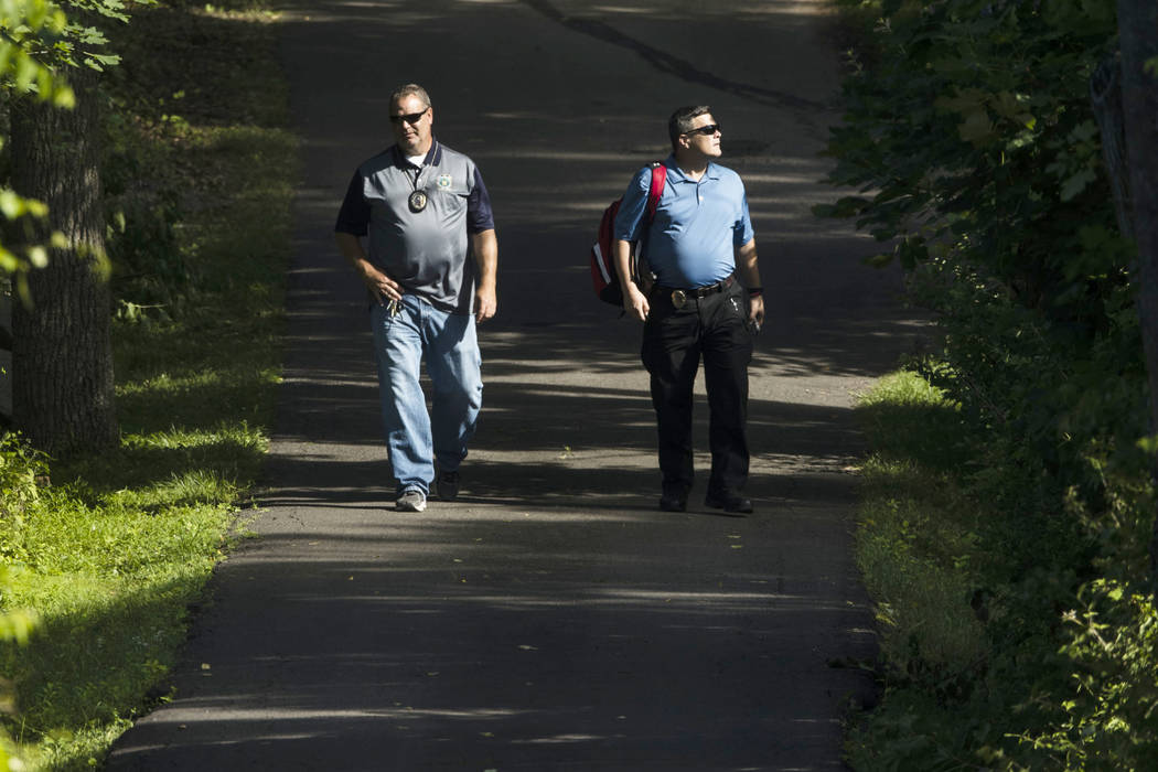 Men walk down a blocked off drive way, in, Solebury, Pa., as the search continues Wednesday, July 12, 2017, for four missing young Pennsylvania men feared to be the victims of foul play. (AP Photo ...