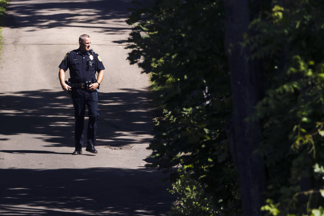 An officer walks down a blocked off drive way, in Solebury, Pa., as the search continues Wednesday, July 12, 2017, for four missing young Pennsylvania men feared to be the victims of foul play. (A ...