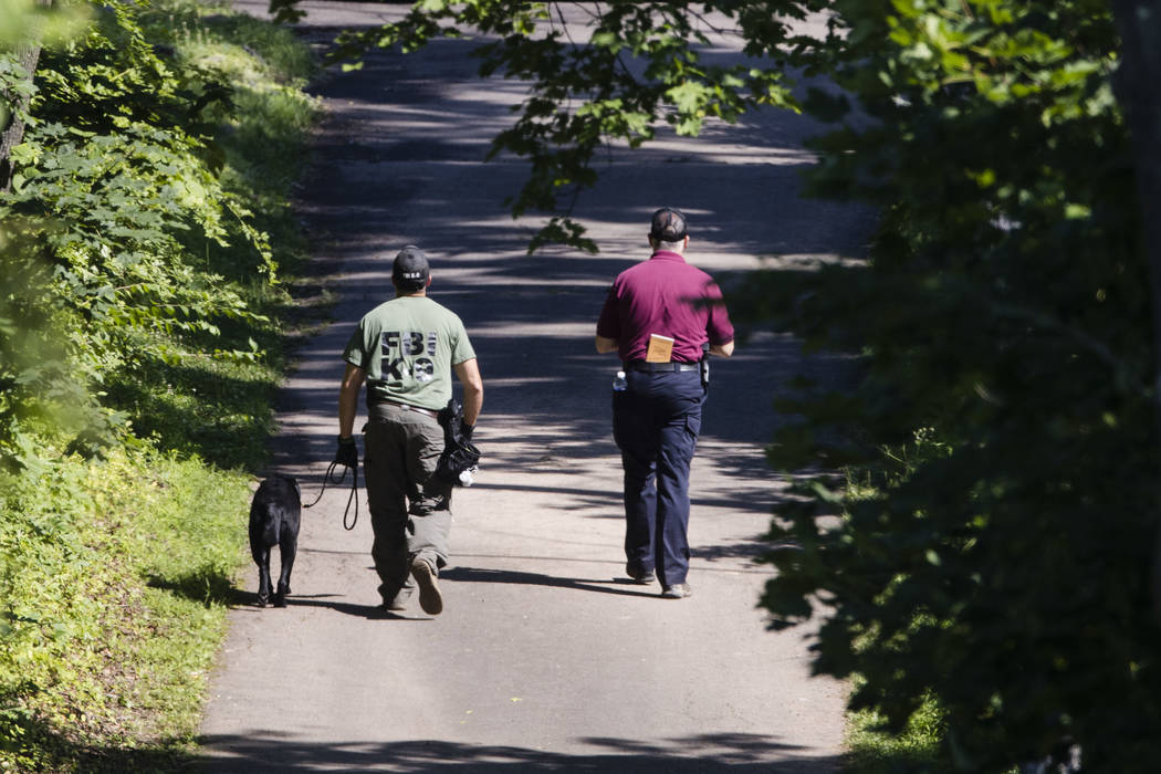 Investigators walk up a blocked off drive way, in, Solebury, Pa., as the search continues Wednesday, July 12, 2017, for four missing young Pennsylvania men feared to be the victims of foul play. ( ...