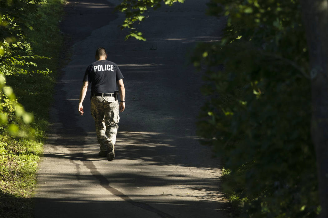 An officer walks up a blocked off drive way, in, Solebury, Pa., as the search continues Wednesday, July 12, 2017, for four missing young Pennsylvania men feared to be the victims of foul play. (AP ...