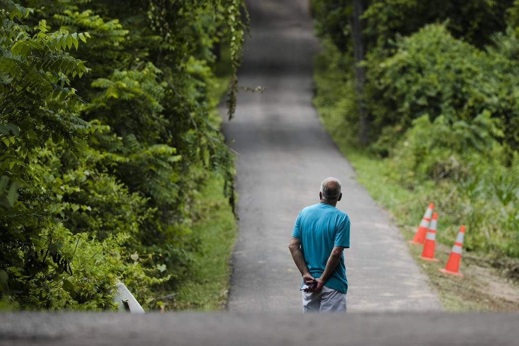 A man looks up a blocked off drive way, in, Solebury, Pa., as the search continues Wednesday, July 12, 2017, for four missing young Pennsylvania men feared to be the victims of foul play. (AP Phot ...