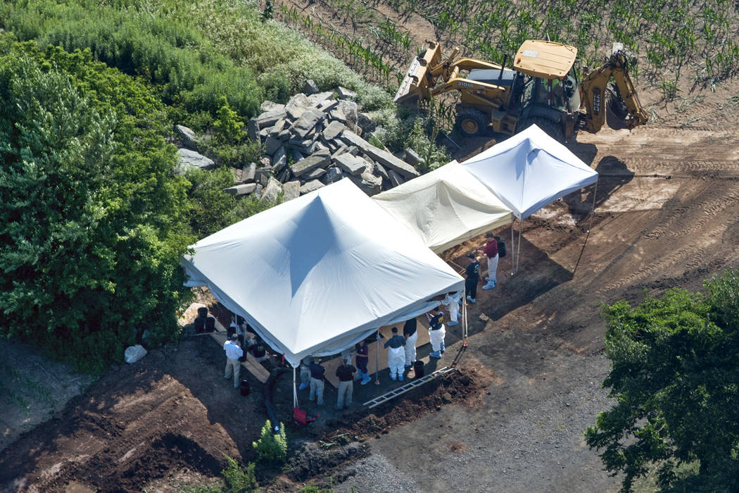 Investigators gather under tents as they search a property, Wednesday, July 12, 2017, in Solebury, Pa., for four missing young Pennsylvania men feared to be the victims of foul play. (Clem Murray/ ...