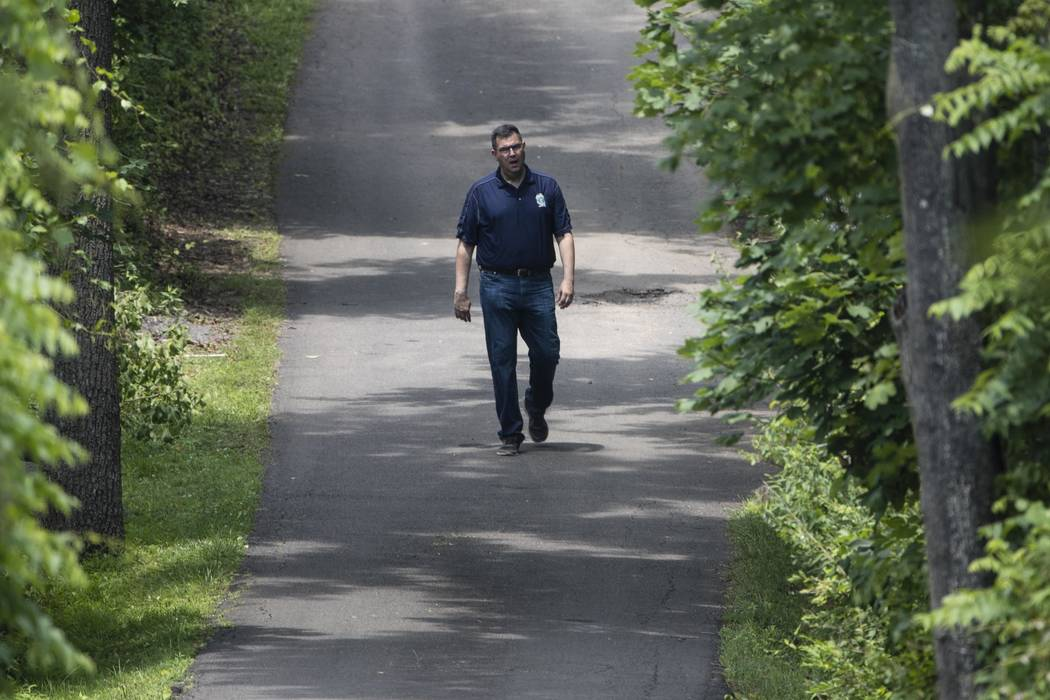 Gregg Shore, First Assistant District Attorney for Bucks County, Pa., walks down a driveway, Wednesday, July 12, 2017, in Solebury, Pa., as the search continues for four missing young Pennsylvania ...