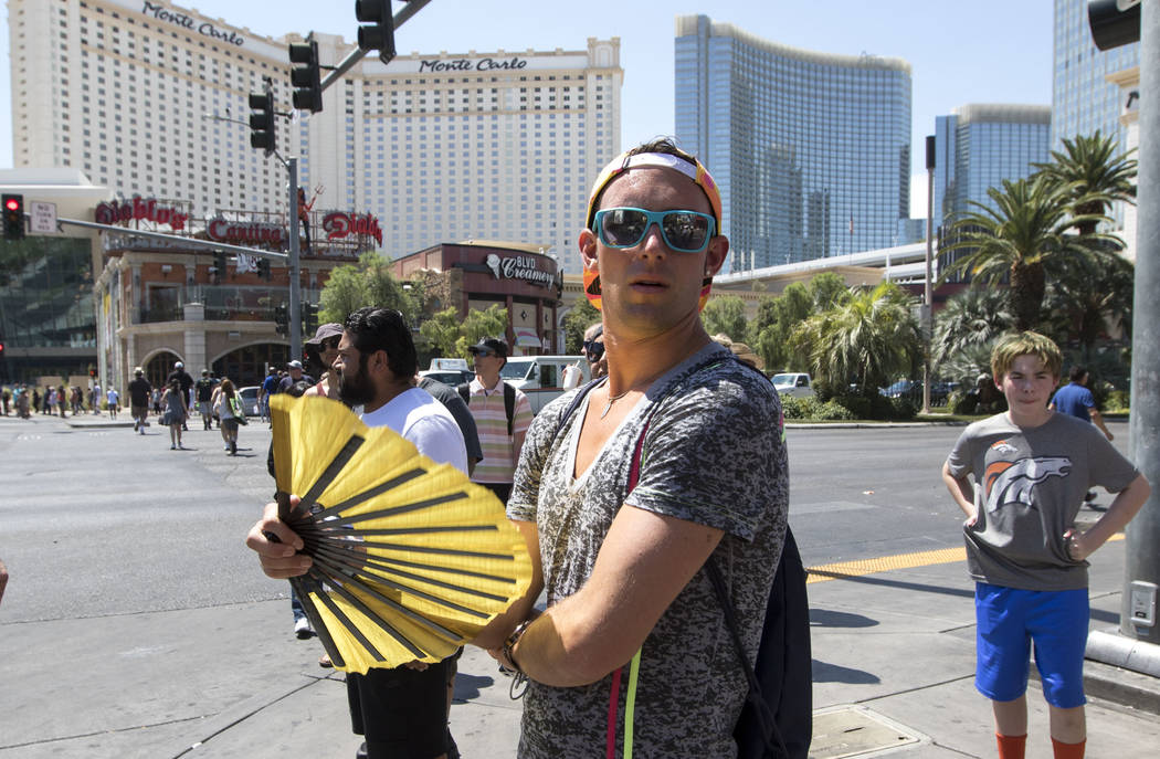 A man waves a fan to cool off during a warm and sunny day along The Strip on Monday, June 19, 2017. (Richard Brian/Las Vegas Review-Journal) @vegasphotograph