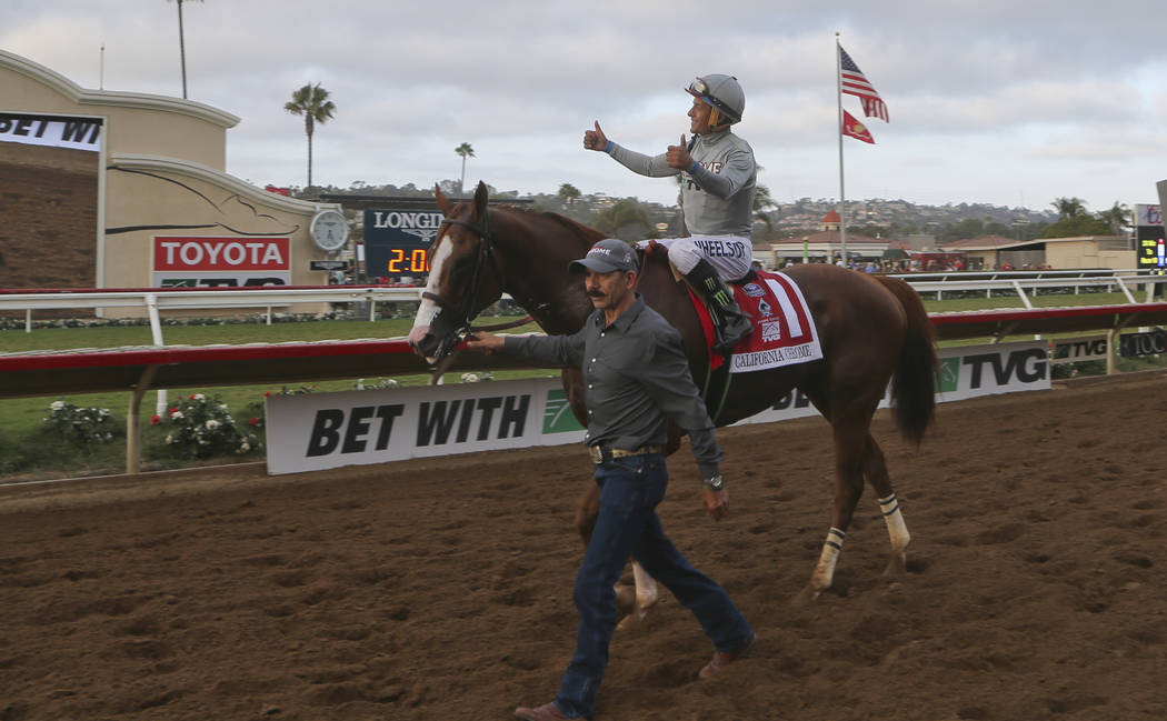 California Chrome, with jockey Victor Espinoza aboard, cools off after winning  the Pacific Classic at Del Mar Thoroughbred Club Saturday, Aug. 20, 2016, in Del Mar, Calif. (AP Photo/Lenny Ignelzi)