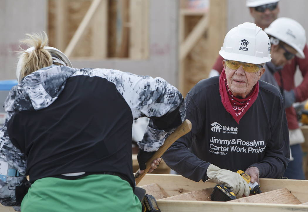 Former President Jimmy Carter and a volunteer help build stairs for a homes for Habitat for Humanity in Edmonton Alberta, Tuesday, July 11, 2017. (Jason Franson/The Canadian Press via AP)