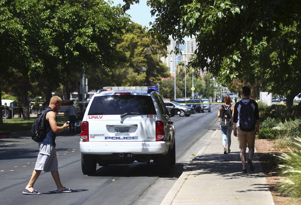Students walk by as UNLV police investigate the scene where gunshots were fired at a parked truck from a car on the UNLV campus in Las Vegas on Thursday, July 13, 2017. Chase Stevens Las Vegas Rev ...