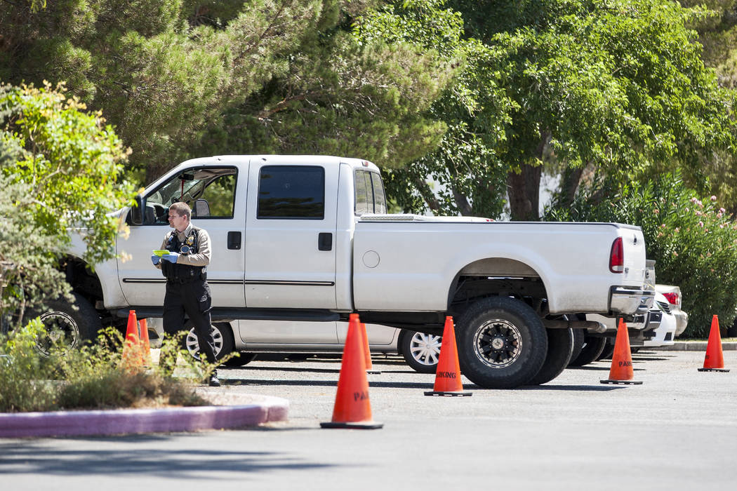 A Metropolitan Police officer inspects a white Ford pickup truck after a woman and her 11-year-old daughter were shot at inside the truck on the campus of UNLV on Thursday, July 13, 2017.  Patrick ...