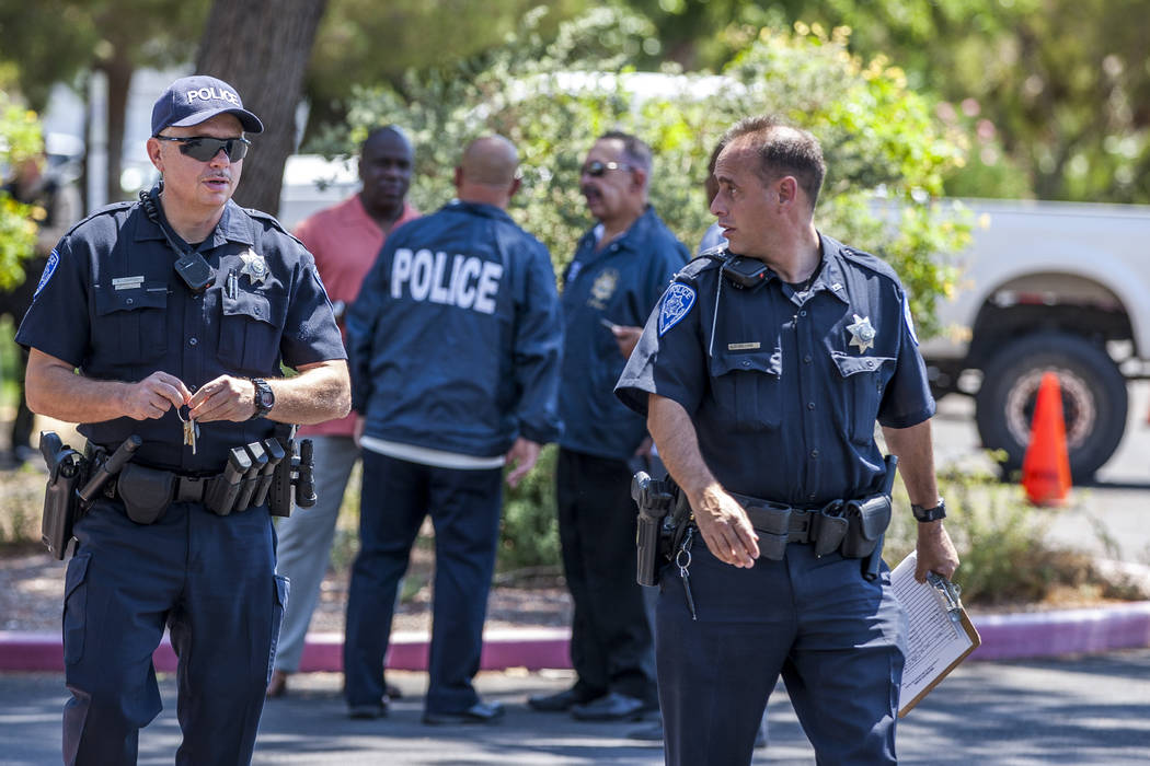 UNLV police officers walk around a crime scene after a woman and her 11-year-old daughter were shot at inside their white Ford pickup truck on the campus of UNLV on Thursday, July 13, 2017.  Patri ...