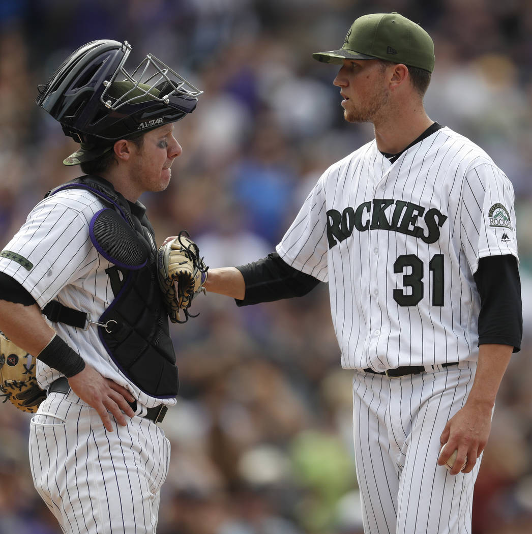 Colorado Rockies catcher Ryan Hanigan (30) and Colorado Rockies starting pitcher Kyle Freeland (31) confer after Freeland's no-hit bid was broken up by a single off the bat of Chicago White Sox le ...