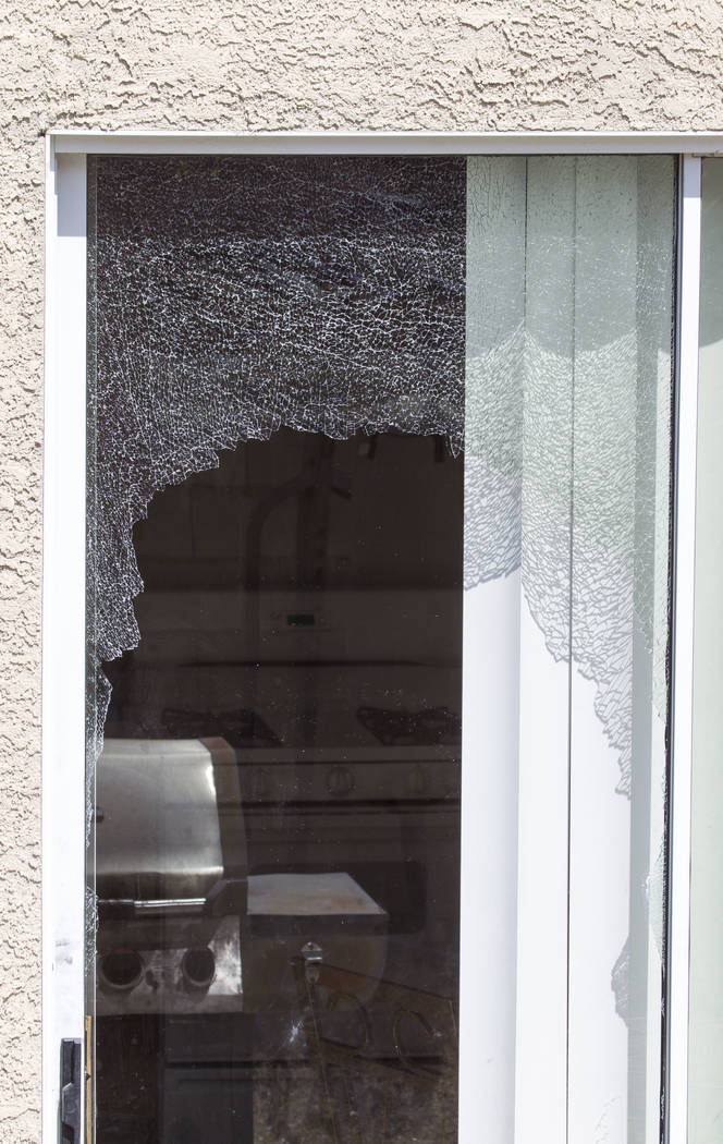 A shattered sliding glass door at a residence in the 5000 block of Droubay Drive in the Squire Village in Las Vegas on Thursday, July 13, 2017.  Neighbors called the police on Wednesday after they ...