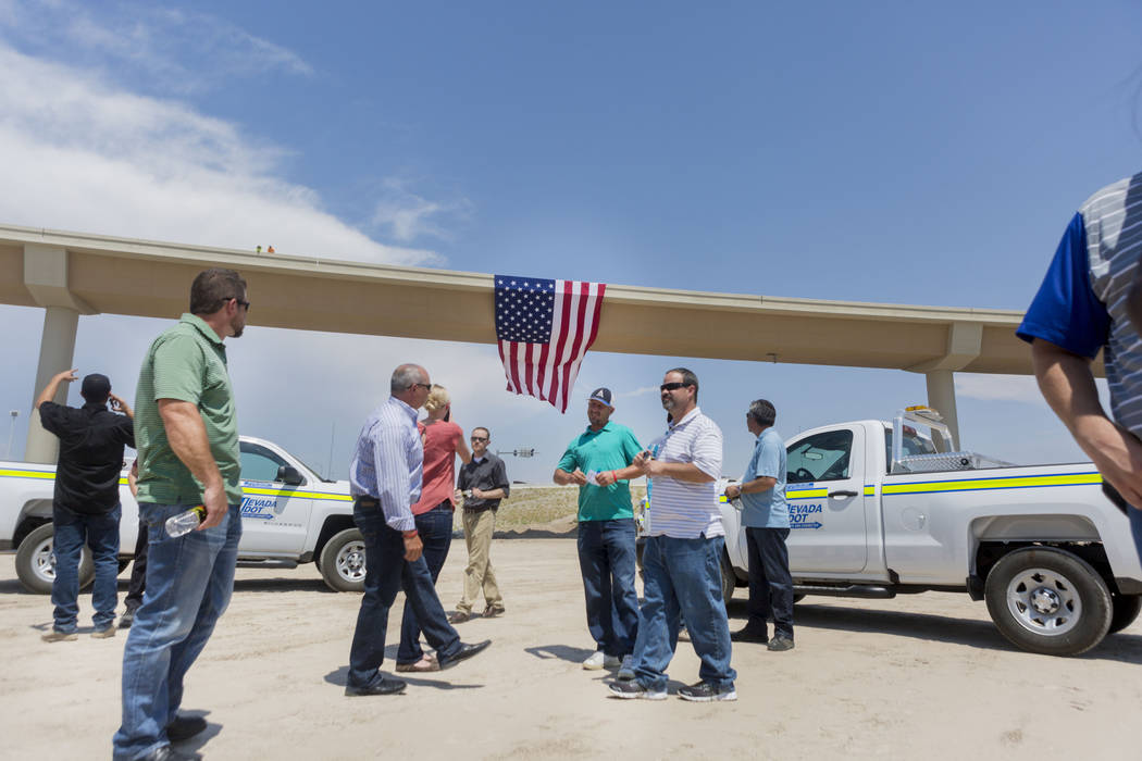 Employees with the Nevada Department of Transportation and Las Vegas Paving Corp. celebrate the opening of the Centennial Bowl flyover bridge linking westbound 215 Beltway and southbound U.S. High ...