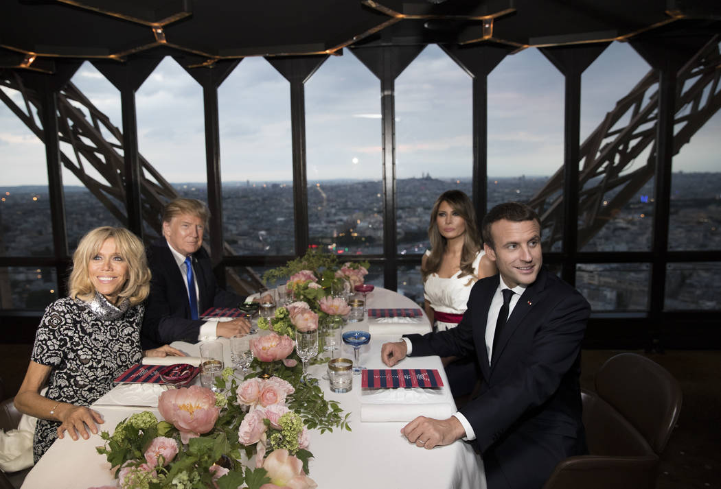 President Donald Trump, first lady Melania Trump, French President Emmanuel Macron and his wife Brigitte Macron are photographed as they sit for dinner at the Jules Verne Restaurant on the Eiffel  ...