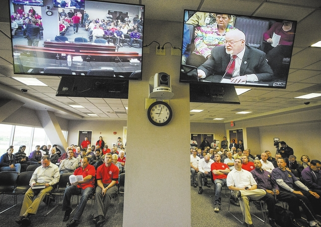 People listens while Assemblyman Randy Kirner, R-Reno,right on monitor, speaks during the Assembly Ways and Means Committee telecast hearing on AB190 hearing  Wednesday, April 15, 2015 at the Sawy ...