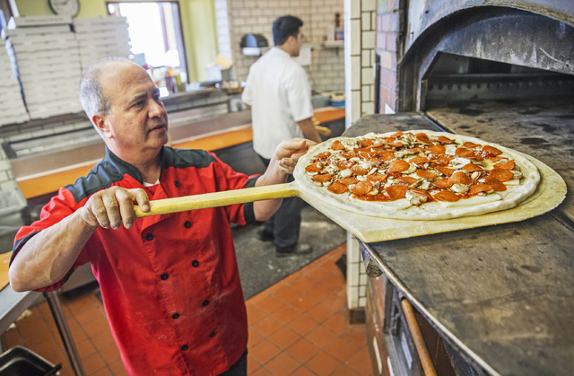 "Chef/co-owner John Arena slides an Olde New York specialty pizza in the oven for seven minutes of cook time on Thursday, Feb. 2, 2017, at Metro Pizza, in Henderson. ""It's not about what's on your  ..."