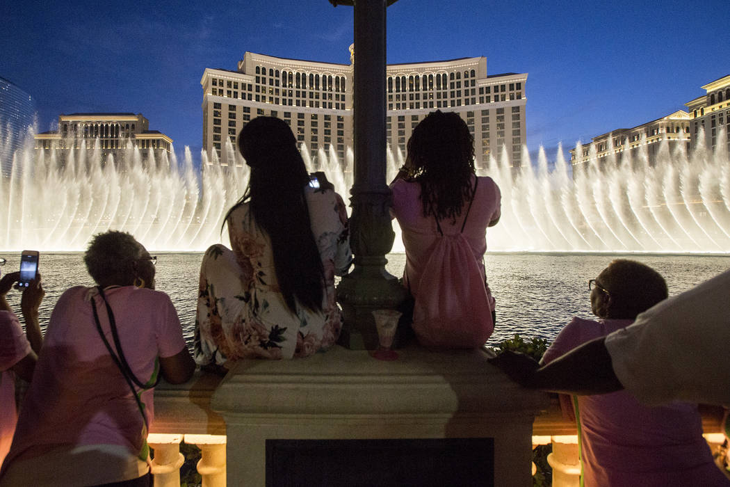 Members of Alpha Kappa Alpha Sorority gather at the Bellagio Fountains for their leadership conference's opening ceremony on Thursday, July 13, 2017, in Las Vegas. The fountains were illuminated g ...