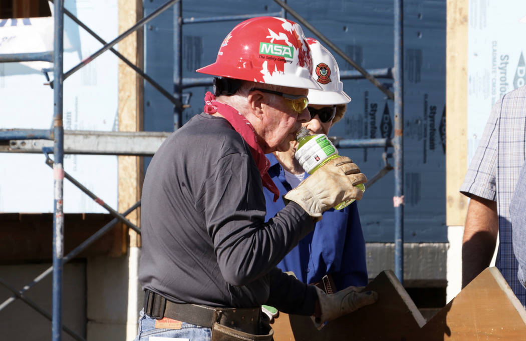 In this photo provided by the Manitoba Government, former U.S. President Jimmy Carter drinks while helping build homes for Habitat for Humanity in Winnipeg, Manitoba on Thursday, July 13, 2017. Ca ...