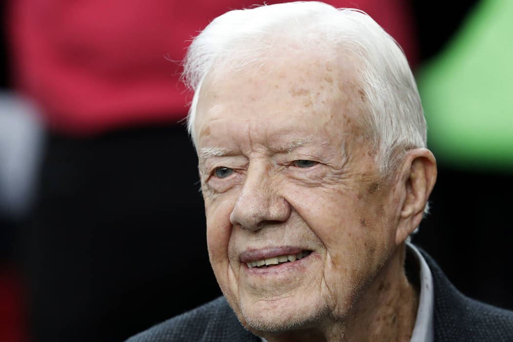 Former President Jimmy Carter sits on the Atlanta Falcons bench before the first half of an NFL football game between the Atlanta Falcons and the San Diego Chargers, in Atlanta on Oct. 23, 2016.   ...