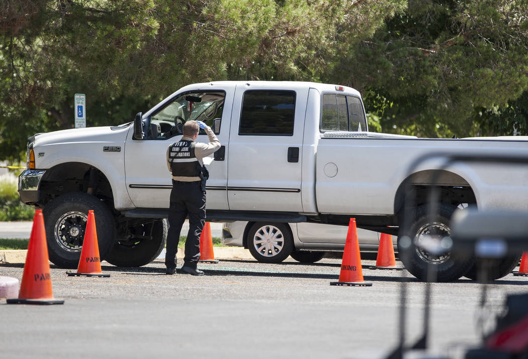 A Metropolitan Police officer inspects a white Ford pickup truck after a woman and her 11-year-old daughter were shot at inside the truck on the campus of UNLV on Thursday, July 13, 2017. (Patrick ...